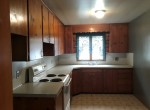 The kitchen has wooden cabinetry, an electric oven,